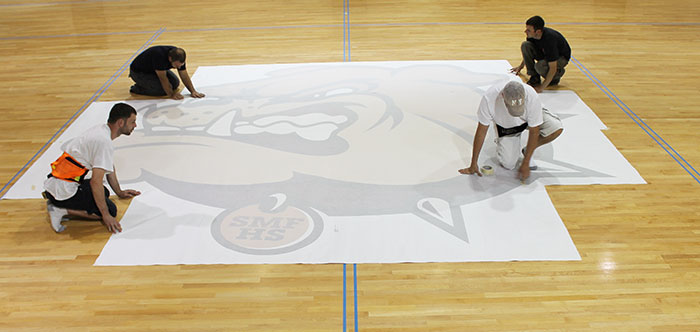 Preparing installation of court graphic